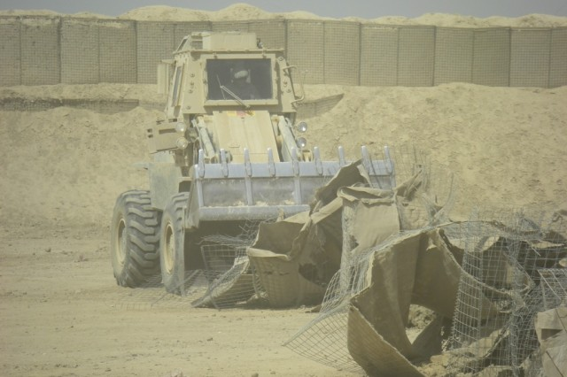 BAGHDAD - Spc. Joshua Carrington of Oneonta, N.Y., heavy equipment   operator, 46th Engineer Combat Battalion (Heavy), 225th Engineer Brigade,   operates the bucket loader to remove HESCO barrier debris from the old   range separation berm and away from the project site in preparation for the setup   of the new range separation wall July 9 at Task Force Raptor here.