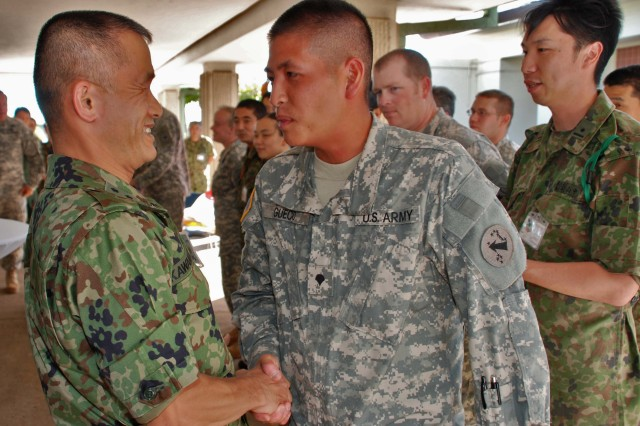 "FORT SHAFTER, HawaiiAca,!""  Maj. Gen. Hiromichi Kawamata, Deputy Chief of Staff, Japan Ground Self Defense Force Northern Army, shakes hands with Spc. Brent Gueco, U.S. Army, Pacific, Contingency Command Post."