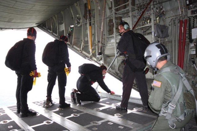 Staff Sgt. Dewey Vinaya remains in contact with the flight crew and Team Leader, Sgt 1st Class, Dave Rose, as he checks out the drop zone and team members await the go ahead to release the Wind Drift Indicators (WDIs).
