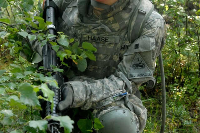 Sgt. Andrew Haase, a Soldier with the 146th Signal Company based in Weisbaden, Germany, searches for enemy movement during a training exercise at the Joint Multinational Training Command located in Grafenwoehr, Germany, July 16. The exercise was part of the Warrior Leader Course evaluation phase at the 7th Army Noncommissioned Officer Academy.