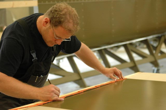 An employee at the Training Aids Production Center (TAPC) in Grafenwoehr, Germany measures an aluminum sheet that will side one of three mock Chinooks being built to train Soldiers throughout Europe. The CH-47 is being made with plywood, steel and aluminum siding. The training device can hold up to 5,000 pounds and will help create a realistic combat environment for Soldiers.