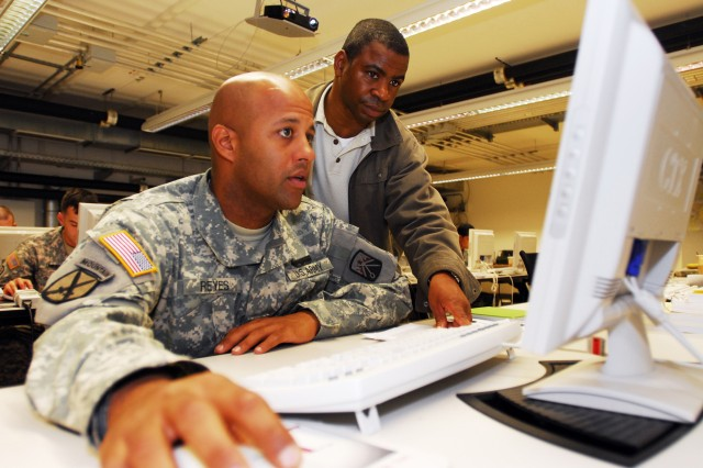 """Staff Sgt. Aljandro Reyes, a driver with the 41st Transportation Co., learns the Blue Force Tracker system on the """"white box"""" simulation computer while Eddie Hill, a digital systems instructor looks on. The Soldiers were attending the Joint Multinational Simulation Center's Digital University to learn or brush-up on their skills with the satellite positioning system in Grafenwoehr, Germany, June 15."""