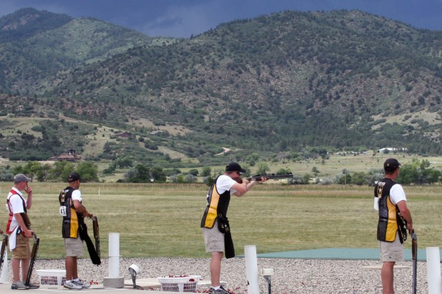 Under threatening skies, Staff Sgt. Josh Richmond, U.S. Army Marksmanship Unit, fires on his target during the finals of the double trap event, July 13, at the U.S. National Shotgun championships. Richmond outlasted the field and the elements to claim the gold medal.