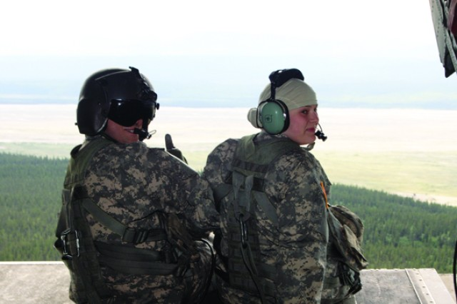 """Spc. Jeffrey Slaughter gives a thumbs up as he and Kayla Collyer-Platzer sit on the rear ramps of CH-47 Chinook flying near the Delta River.  Collyer-Platzer, 15, has third stage Hodgkin's lymphoma. She flew in the Chinook as part of being a """"soldier for a day,"""" courtesy of her soldier-sister."""
