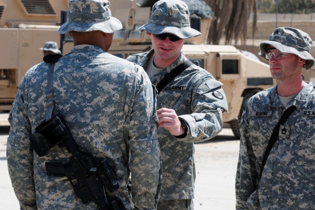 BAGHDAD - Second Lt. Bruce Riggins, from King, N.C., a platoon leader in Company B, 252nd Combined Arms Battalion, 30th Heavy Brigade Combat Team, attaches the brigade patch to the uniform of Spc. Ricky Dixon, of Charlotte, N.C., as platoon sergeant Sgt. 1st Class Christopher Mooring, of Pine Level, N.C., watches. Company B Soldiers received their combat patches during a ceremony at Joint Security Station Saydiyah, in Baghdad, July 19. The entire battalion received their combat patches in ceremonies that day.