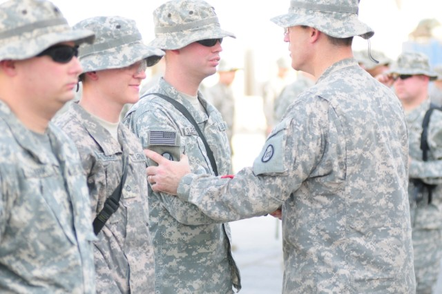 BAGHDAD - Spc. Charles Clements, of Gastonia, N.C., receives the brigade combat patch from Brigade Commander Col. Greg Lusk as fellow Company C, 252nd Combined Arms Battalion, 30th Heavy Brigade Combat Team Soldiers Pfc. Jeremy Hester, of Asheville, N.C. (center), and Spc. John Clark, of Sanford, N.C., wait to receive theirs during a ceremony at Forward Operation Base Falcon, located at the southern edge of Baghdad, July 19. All Soldiers of the 252nd CAB received their patches at ceremonies that day from other brigade and battalion leaders.