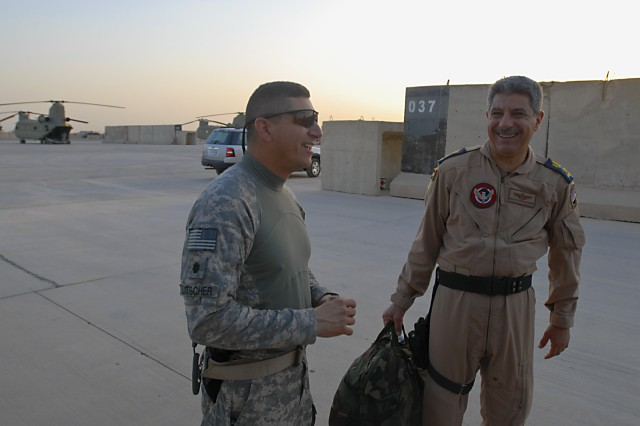 TAJI, Iraq- Lt. Col. Ralph Litscher, from Galf Moon Bay, Calif., commander, 2nd Battalion, 227th Aviation Brigade, 1st Air Cavalry Brigade, 1st Cavalry Division, Multi-National Division - Baghdad, shares a laugh with Lt. Col. Jassim Mohammed, Squadron 15, Iraqi Air Force, Al Taji airbase, before both men fly out on CH-47F Chinook helicopters to observe a daytime air assault, July 20, at Camp Taji, Iraq.