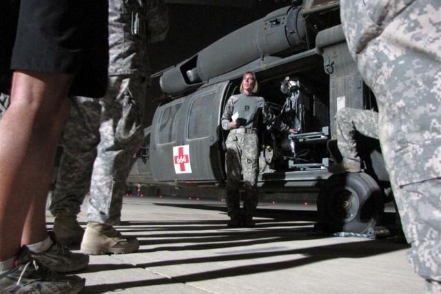Sgt. Merissa Merlin, from Portland, Ore., a flight medic with the Oregon Army National Guard's Charlie Company 7th Battalion, 158th Aviation Regiment, describes a litter configuration on a UH-60 Black Hawk during medical evacuation training. The training included Oregon Army National Guard Soldiers and Washington Army National Guard's 1st Battalion, 161st Infantry Regiment medical Soldiers at Joint Base Balad, Iraq
