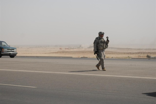 FALLUJAH, Iraq - Staff Sgt. Theodore Montgomery, a squad leader in B Company, 2nd Battalion 142nd Infantry, 56th Infantry Brigade Combat Team, directs traffic during recovery operations after a vehicle breakdown on the outskirts of Fallujah, June 24. Montgomery, serving in his second tour to Iraq, has been on the road executing the convoy escort mission to a tune of more than 20,000 miles in only seven months.