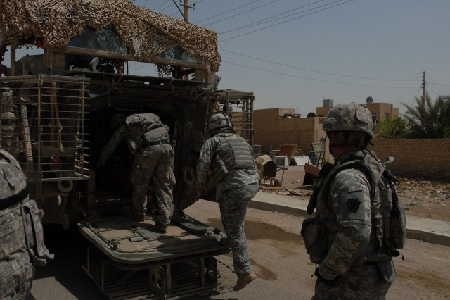 TAJI, Iraq - Pennsylvania Army National Guard Soldiers climb into the rear of a Stryker vehicle in Sab al Bour, southwest of Taji, and north of Baghdad July 20. The Soldiers are from A Troop, 2nd Squadron, 104th Cavalry Regiment, 56th Stryker Brigade Combat Team.