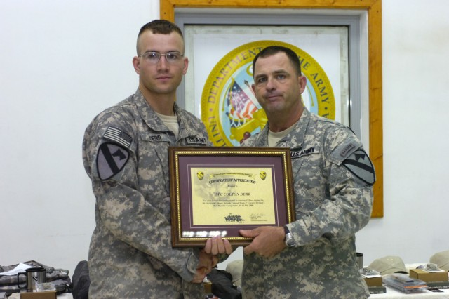Command Sgt. Maj. James Pippin, the command sergeant major of the 3rd Heavy Brigade Combat Team, 1st Cavalry Division, presents Spc. Colton Derr, the enlisted Soldier representing 6th Squadron, 9th Cavalry Regiment, for being the junior enlisted winner of the brigade's Warrior competition.