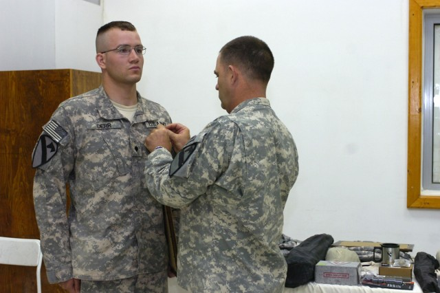 Command Sgt. Maj. James Pippin, the command sergeant major of the 3rd Heavy Brigade Combat Team, 1st Cavalry Division, presents Spc. Colton Derr, the enlisted Soldier representing 6th Squadron, 9th Cavalry Regiment, with an Army Commendation Medal for being the junior enlisted winner of the brigade's Warrior competition.