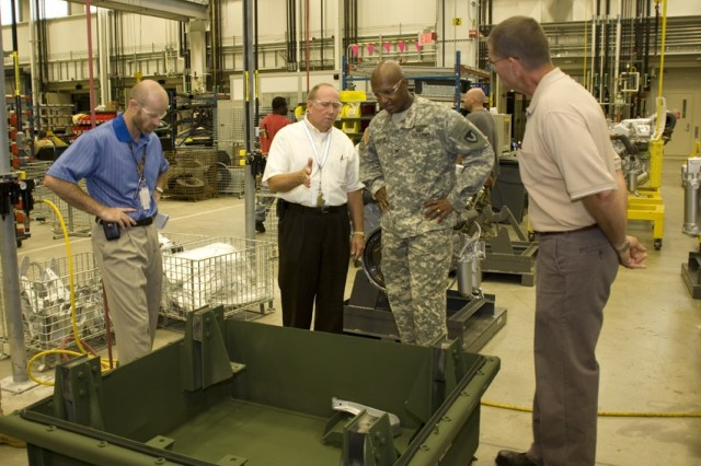Inside the Powertrain Flexible Maintenance Facility, Deputy to the Commander Jack Cline expounds on the capabilities of the facility to AMC's Chief of Public and Congressional Affairs Col. Henry Huntley.  Looking on are (l) Depot Chief of Staff Phillip Trued and (r) Ricky Dale Smith, production management specialist.
