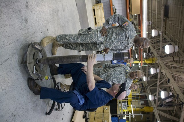 Col. Henry Huntley (left) thanks depot employee Chris Hurst for the work he performs on small arms equipment. Joining him is depot Sgt. Maj. Tony Butler.