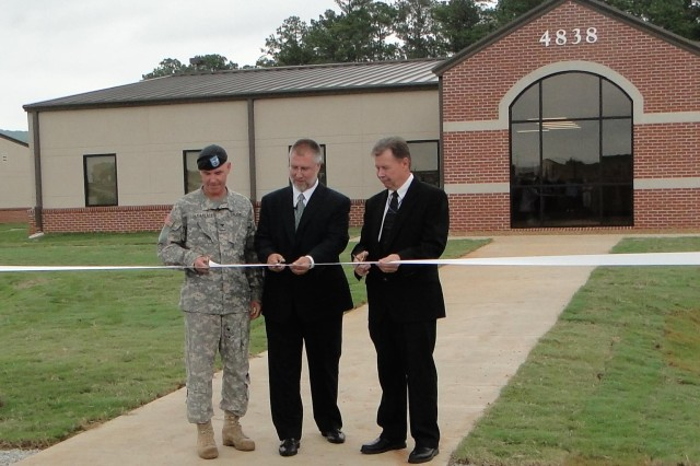 Col. Chris Sullivan, commander of the Aviation Technical Test Center, is joined by Rusty Weiger, deputy program executive officer for aviation, and Joe Davis, Garrison director of public works, to cut the ribbon on two buildings at the Combined Test Team Development Flight Test Complex at the Redstone Airfield.