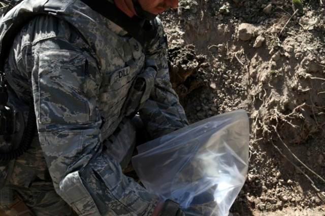 LOGAR PROVINCE, Afghanistan-- U.S. Air Force Staff Sgt. Carl Dill bags up remains of a controlled Improvised Explosive Device in Logar province, Afghanistan, July 15. Dill is currently serving with the 741st Explosive Ordnance Device Battalion, Task Force Spartan, 3rd Brigade Combat Team, 10th Mountain Division. (Photo by U.S. Army Pfc. Richard W. Jones Jr., 55th Signal Company)