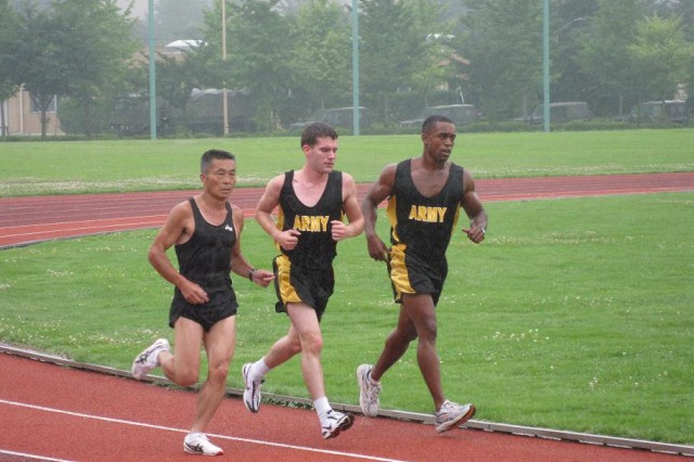 """CAMP ASAKA, Japan-On July 21, 2009 the U.S. Army Japan 10 mile running team members 1Lt Darrius Glover, right, and Spc. Wilbert Litzinger, center, traveled to the Japanese Defense Service Physical Training School here for an initial assessment from JSD Olympic running coach, Major Yoshio Tani. The school, which trains all JSDF Olympic athletes, agreed to assist training the USARJ team for the Army's annual 10 miler race. Coach Tani reviewed their run times and diet. Then he looked at their work schedule and developed a training program around it. Coach Tani took the runners on a """"quick"""" 4 kilometer run to assess their physical fitness and running style. The 56 year old Tani said their 4 minute per kilometer average was """"not bad"""" for starting out and was sure they can improve their times. U.S. ARMY JAPAN PHOTO"""