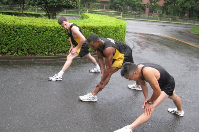 From left: Japan Self Defense Olympic running coach, Major Yoshio Tani, leads cool down stretches with U.S. Army Japan10 Miler run team members 1Lt Darrius Glover and Spc. Wilbert Litzinger at the JDS Physical Training School at Camp Asaka July 21, 2009. U.S. ARMY JAPAN PHOTO
