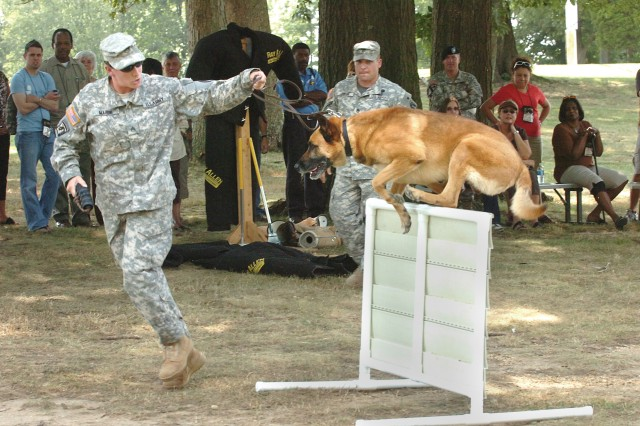Staff Sgt. Elizabeth Marini, 212th Military Police Department maneuvers her dog through an obstacle course for the San Antonio Educators Friday at Parade Field 2.