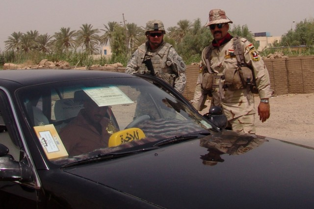 MAHMUDIYAH, Iraq -- Sgt. Jefery Fyke of Fayetteville, N.C., a driver with Company B, 120th Combined Arms Battalion, 30th Heavy Brigade Combat Team, and an Iraqi Soldier with 3rd Company, 3rd Battalion, 17th Iraqi Army Division, conduct a traffic stop in a rural area near Mahmudiyah, Iraq, south of Baghdad, July 21. Through the use of traffic control points, Iraqi Security Forces protect the local populace by keeping insurgent groups from smuggling weapons into areas throughout Iraq.