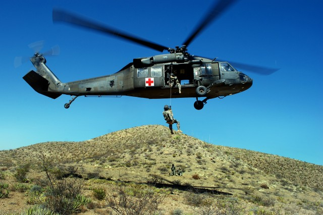 Sergeant Robert Smith, Company C MEDEVAC, 2nd Battalion, 3rd Aviation Regiment, is hoisted by a MEDEVAC Black Hawk as Sgt. Matt Gomes, also with C Co., guides the hoist during Falcon Focus, a training exercise at Camp McGregor, Fort Bliss, Texas that concluded, July 2.