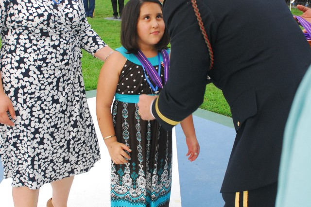 Vivianaiy Cimarrusti, daughter of Staff Sgt. Ernesto Cimarrusti, receives the Gold Medal of Remembrance from Maj. Gen. Tony Cucolo, 3rd ID Commanding General, during a ceremony, July 18 at Cottrell Field on Fort Stewart.