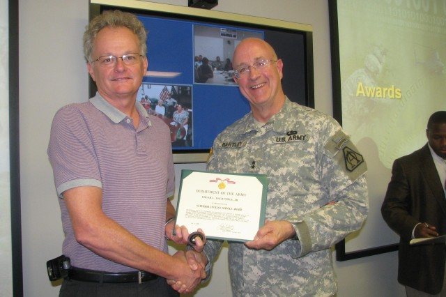 Edgar Dalrymple, FCS associate director for software engineering, Software Engineering Directorate, Aviation and Missile Research Development and Engineering Center, receives the Superior Civilian Service Award and FCS Coin from Maj. Gen. John Bartley, program manager for Future Combat System. The ceremony was held July 15 in Warren, Mich. After serving seven years in his current position, Dalrymple has accepted a Senior Service College Fellowship at the Defense Acquisition University, Huntsville Campus.