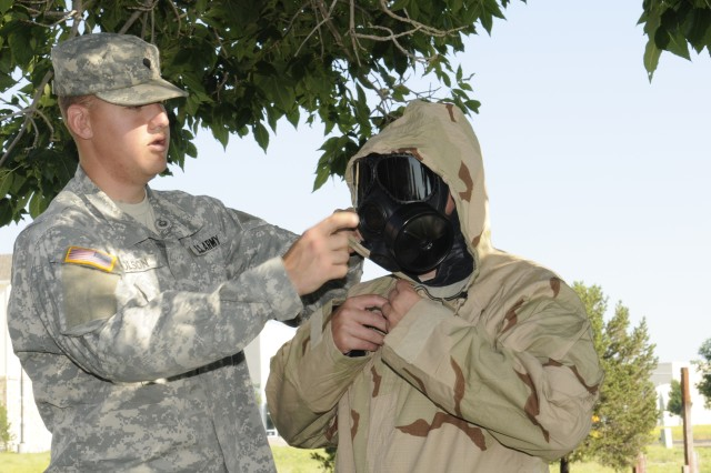 "Spc. Dennis Olson, Nuclear, Biological and Chemical Specialist, Headquarters Company, 1st Space Brigade, instructor for this Army Warrior Training task, acts as a ""buddy-assistor"" while a Soldier from the 100th Missile Defense Brigade (Ground-based Midcourse Defense) suits up in Mission Oriented Protective Posture 4."