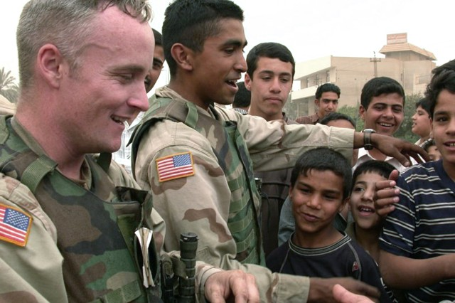 Iraqi children gather around 1st Sgt. CJ Grisham, left, and his interpreter, Sgt. Larry Alvarez, as they hand out candy in a goodwill gesture while touring Fallujah, Iraq in 2003.