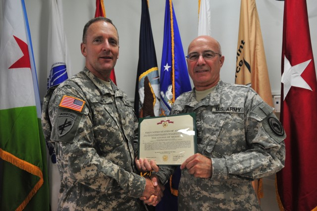 Brig. Gen. Chris Leins (left), Combined Joint Task Force - Horn of Africa deputy commander, presents Sgt. Maj. Samuel Stoner with the Legion of Merit Medal, July 21, 2009, for exceptionally meritorious service during his 40-year military career. Stoner was deployed for more than 11 months to Djibouti as the joint intelligence chief and senior enlisted advisor.