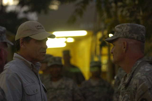 "Texas Gov. Rick Perry, talks with a Texas national guardsman, July 20, at Bagram Air Field. Perry thanked the National Guard Soldiers from the 6th Battalion, 36th Military Intelligence Brigade, out of Camp Mabry, Texas, for their service and said ""everyone back home is proud of what y'all are doing."" (Photo by U.S. Army Pfc. Derek L. Kuhn, 40th Public Affairs Detachment)"