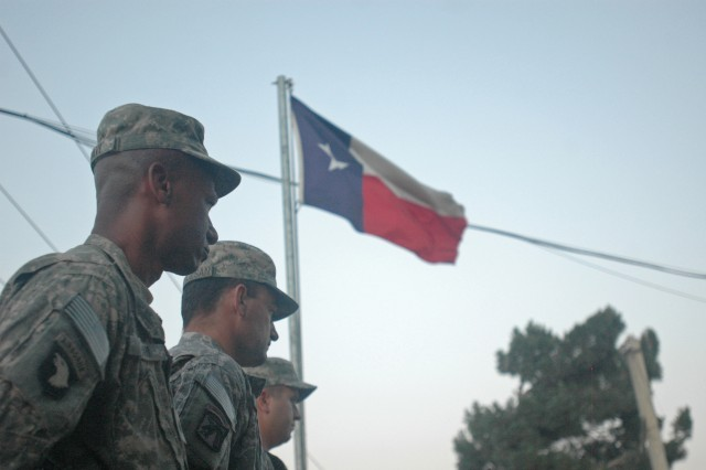 National Guard Soldiers from the 6th Battalion, 36th Military Intelligence Brigade, out of Camp Mabry, Texas, stand at parade rest during a flag raising ceremony at Bagram Air Field, July 20. Gov. Rick Perry, the governor of Texas, was on hand to see his national guardsmen raise the new Texas flag. (Photo by U.S. Army Pfc. Derek L. Kuhn, 40th Public Affairs Detachment)