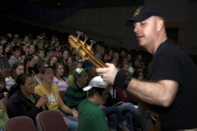 Sgt. 1st Class Pete Krasulski plays bass guitar for The Volunteers.