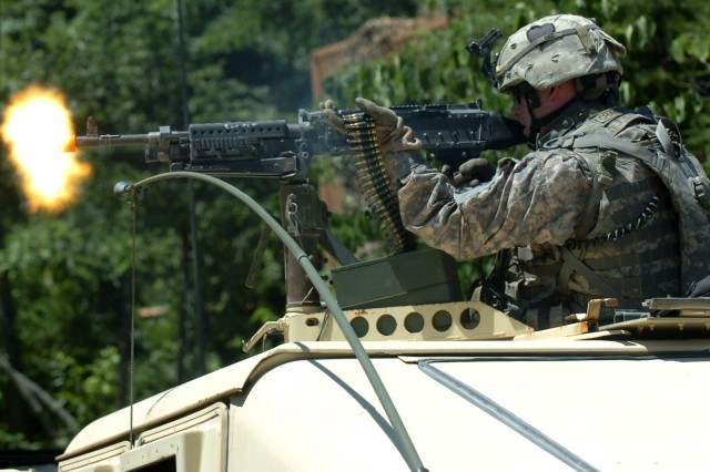 Specialist Cody Chandler, a team member with Charlie Company, 1st Squadron, 75th Cavalry Regiment, 2nd Brigade Combat Team, 101st Airborne Division, is returning fire with a mounted M-240B machine gun while patrolling a hostile village training course, July 13. The 1-75th conducted Eagle Flight One training, a series of team building exercises, while at Fort Knox for 11 days.