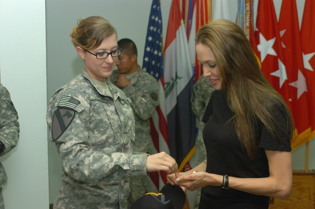 BAGHDAD - Fargo, N.D. native, Sgt. Adrienn Falk, administrative assistant to the commanding general, 1st Cavalry Division, Multi-National Division-Baghdad, presents a 1st Cav. Div. hat and division coins to actress and United Nations Goodwill ambassador Angelina Jolie July 23 during a visit to Camp Liberty, Iraq. Jolie took time to speak with and meet MND-B Soldiers  while in Iraq as an advocate for the rights of refugees.