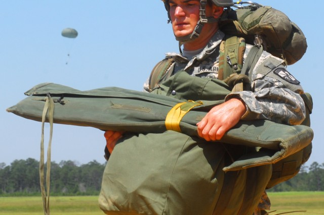 Cadet Garret Rinaman carries his equipment off the drop zone after landing at Fryar Field.