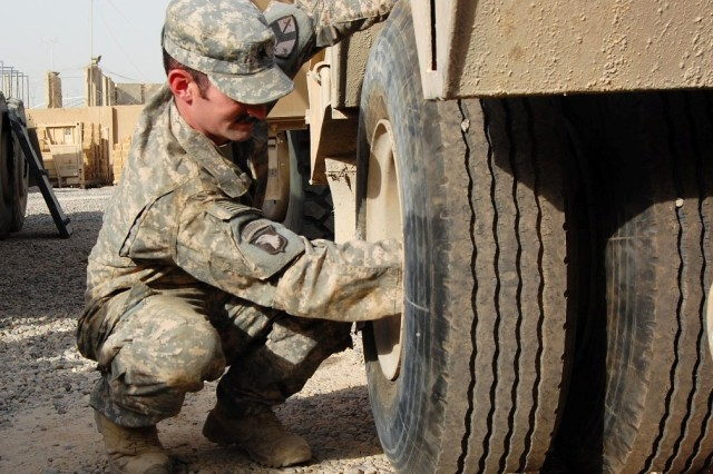 """BAGHDAD - Sgt. David Brown of the 230th Brigade Support Battalion, 30th Heavy Brigade Combat Team checks the bolts on the back tires of a trailer used to haul disabled vehicles in Iraq, July 18. He is the youngest of three brothers serving on their second tour together in Iraq. He repairs the heavy-wheeled vehicles that his brothers David and Jeremy usually drive during this tour. """"The greasier, the dirtier, the better,"""" said Brown, about his job at Camp Stryker. The native of Glenville, W. Va., is serving his third overseas deployment."""