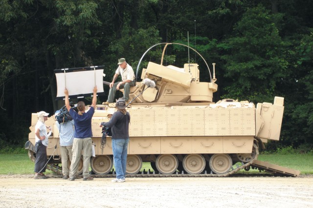 Gunny R. Lee Ermey films a commercial break segment while standing beside a Bradley Fighting Vehicle.