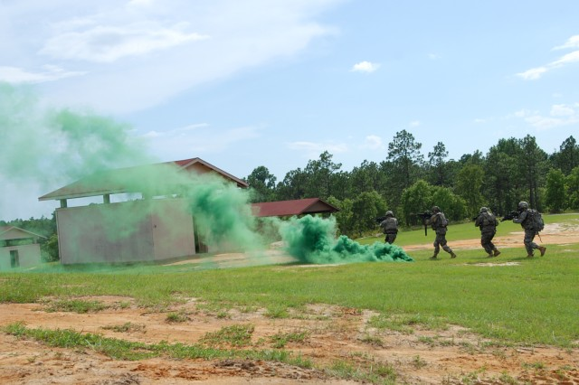 Military Police from Headquarters Company, Brigade Special Troops Battalion, 2nd Brigade Combat Team, 82nd Airborne Division pop green smoke to conceal their movements while searching a village suspected of harboring enemy fighters during the BSTB's convoy live fire training exercise July 22. (U.S. Army photo by Staff Sgt. Mike Pryor, 2nd BCT, 82nd Abn. Div. Public Affairs)