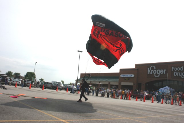 Staff Sgt. Jason Spinnicchia about to land amongst the amazed shoppers at the Kroger Grocery Store parking lot the day before the Prairie Air Show opened in Peoria, IL, to help promote the event.