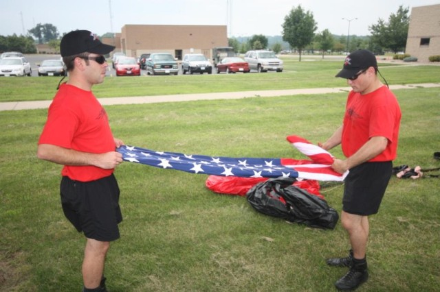 Staff Sgt. Jason Spinnicchia and Sgt. Tony Galusha pay respect to the American Flag after the Black Daggers jumped it in to the Prairie Air Show in Peoria, IL.