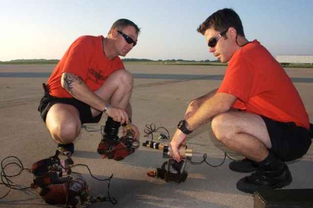 Sgt. 1st Class Dave Rose and Staff Sgt. Jason Spinnicchia prepare the smoke canisters before their jump into the Prairie Air Show, Peoria, IL.