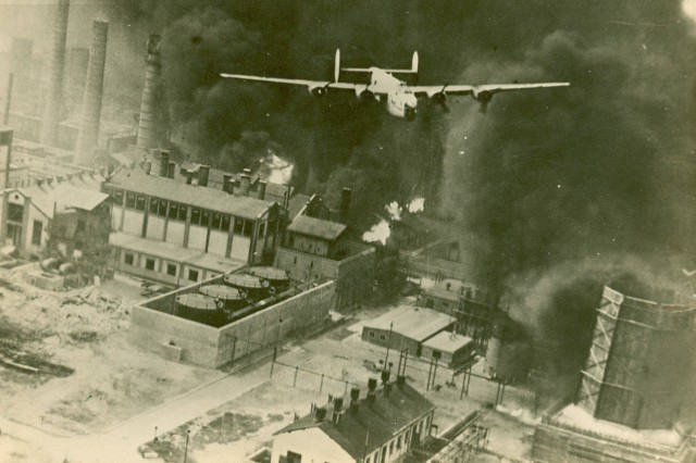 Air Raid Ploesti! A B-24 flying over a burning oil refinery at Ploesti, Rumania, 1 August 1943. (44th Bomb Group Photograph Collection).