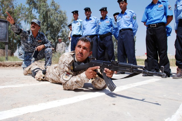 Capt. Hayder Adnan Ali, Iraqi police liaison to coalition forces, instructs trainees on proper shooting techniques from the prone position while Sgt. Hayder Sahib Silan, Iraqi police mobile training team instructor in Wasit province, Iraq, demonstrates at the police provincial headquarters, July 20, 2009.