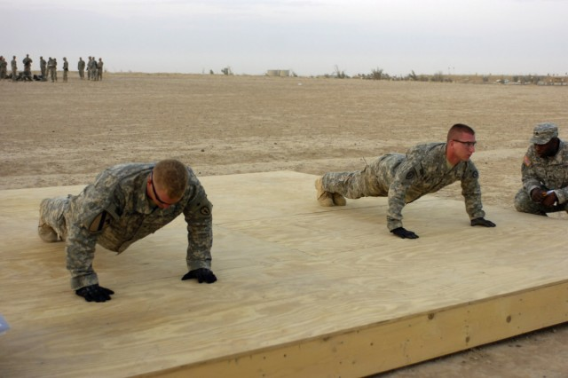"""Soldiers participating in the """"Joint Best Warrior Competition - Multi-National Division - North"""" perform push-up repetitions during the timed push-up portion of the physical fitness test at Contingency Operating Base Speicher, near Tikrit, Iraq, July 27. The competition is part of a 4-day physical and mental trial to find the best warrior currently serving in northern Iraq. (U.S. Army photo by Spc. Jared Sollars, 145th Mobile Public Affairs Detachment)"""