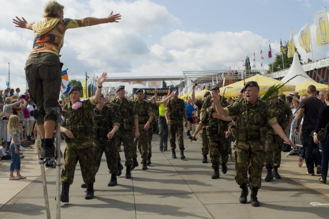 Dutch troops are greeted by a lady on stilts at a turn before the final rest stop at the Four Days March in Cuijk, the Netherlands, July 24. A team of Soldiers from 21st Theater Sustainment Command, along with more than 40,000 others participated in the event.