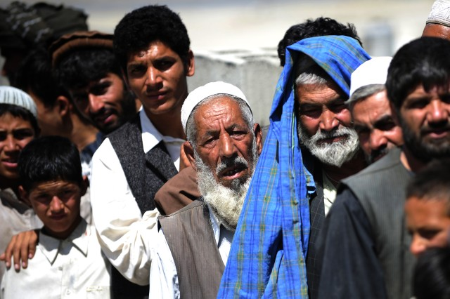 Afghan refugees wait in line to receive bags of donated items, July 24. Combined Security Transition Command - Afghanistan chaplains and coalition forces frequently volunteer to distribute donated clothing, school supplies and food aid to people in need throughout the Kabul area.
