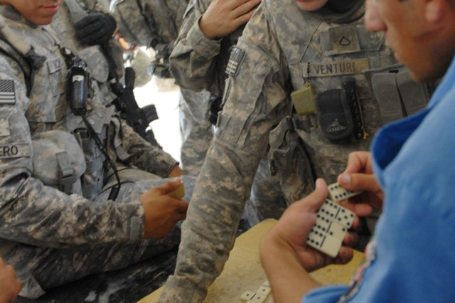BAGHDAD - Staff Sgt. Jonathan Romero (left), a military police squad leader from San Antonio and Sgt. Bianca Leisure, an MP from Douglas, Ariz., look on as Pfc. Shane Venturi (right), a medic from Evansville, Ind., places his dominoes piece during a friendly game with their Iraqi Police partners in western Baghdad, July 24. The game took place during a routine check by the Soldiers of the 591st MP Company, 93rd MP Battalion, 8th MP Brigade, on the al-Walid IP Station.