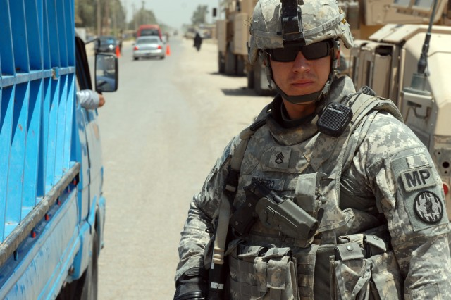 "BAGHDAD - Staff Sgt. Jonathan Romero, a military police squad leader assigned to the 591st MP Company, 93rd MP Battalion, 8th MP Brigade, checks the flow of traffic at an Iraqi Police checkpoint during a routine check in western Baghdad, July 24. ""They do still need a little support from Coalition forces...but as far as training goes and providing security for the community, they're good to go,"" said the San Antonio native."