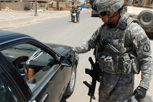 "BAGHDAD - Staff Sgt. Jonathan Romero, a military police squad leader from San Antonio, assigned to the 591st MP Company, 93rd MP Battalion, 8th MP Brigade, hands out Iraqi newspapers in an effort to keep the local citizens informed in the community his unit patrols. ""A lot of the community doesn't view us as bad people,"" said Romero. ""We pass out literature on a weekly basis because it benefits the community and us."""